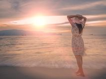 Femme seule et déprimée tenant un chapeau et une position devant la mer Image libre de droits
