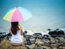 Femme seule et déprimée tenant un parapluie et s'asseyant devant la mer Photo stock