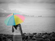 Femme seule et déprimée tenant un parapluie et une position devant la mer Photographie stock