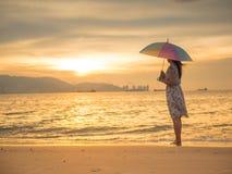 Femme seule et déprimée tenant un parapluie et une position devant la mer Photographie stock libre de droits