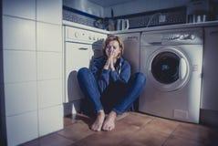 Femme seule et malade s'asseyant sur le plancher de cuisine dans la dépression d'effort et la tristesse images stock