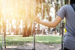 Femme seule manquant son ami tout en balançant en parc Images libres de droits