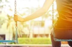 Femme seule manquant son ami tout en balançant dans la villa de parc pendant le matin Photographie stock libre de droits
