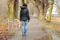 Femme seule marchant en parc le jour pluvieux froid photo stock