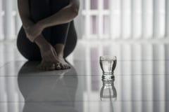 Femme seule s'asseyant avec un verre de l'eau photographie stock