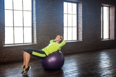 Femme sexy équilibrant sur la boule de forme physique Photographie stock libre de droits
