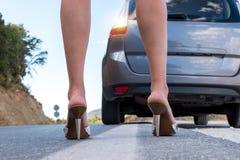 Femme sexy avec de longues jambes se tenant à côté de la voiture Image libre de droits