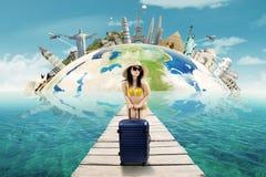 Femme sexy avec des vacances de bikini au monument du monde Image stock