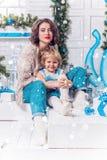 Femme sexy avec du charme avec le rouge à lèvres rouge et sa fille dans un knit Photos stock