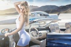 Femme sexy avec la voiture et l'avion de luxe Images stock