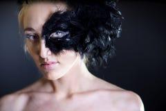 Femme sexy avec le demi masque de plume noire image libre de droits