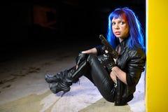 Femme sexy avec les cheveux bleus tenant deux armes à feu et regardant comme tueur Images libres de droits
