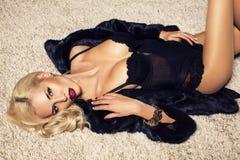 Femme sexy avec les cheveux blonds dans la lingerie et le manteau de fourrure Photographie stock libre de droits