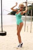 Femme sexy avec les cheveux blonds dans le maillot de bain et des lunettes de soleil posant sur la plage Photographie stock