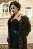 Femme sexy avec les cheveux foncés dans le manteau de fourrure et les gants luxueux images libres de droits