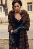 Femme sexy avec les cheveux foncés dans le manteau de fourrure et les gants luxueux photos stock