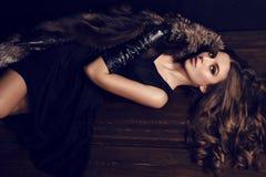 Femme sexy avec les cheveux foncés dans le manteau de fourrure luxueux et les gants en cuir Photos stock