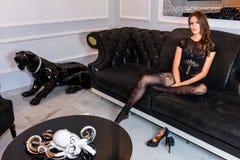 Femme sexy dans la combinaison noire séduisante de lingerie se reposant sur le divan Photo stock
