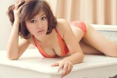 Femme sexy dans la lingerie groveling sur la table Photographie stock libre de droits