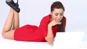 Femme sexy dans la robe rouge se trouvant et fonctionnant banque de vidéos