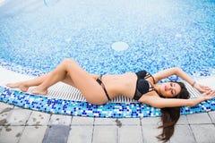Femme sexy dans le bikini appréciant le bain de soleil sur le bord de piscine un jour ensoleillé, vocation d'été Photos libres de droits
