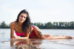 Femme sexy dans le bikini s'étendant dans l'eau photos stock