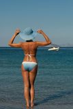 Femme dans le bikini sur la plage regardant loin Photo stock