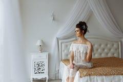 Femme sexy dans les sous-vêtements transparents se reposant sur le lit photo libre de droits