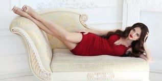 Femme sexy de belle brune dans la robe rouge élégante se trouvant sur le mode Photo stock