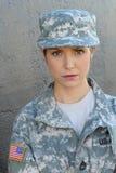 Femme sexy de brune avec le drapeau des Etats-Unis sur l'uniforme d'armée posant au mur gris Images libres de droits