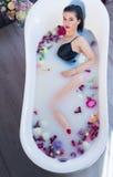 Femme de brune détendant dans le bain chaud de lait avec des fleurs Images libres de droits