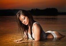Femme sexy de brune dans la lingerie s'étendant en eau de rivière Jeune détente femelle sur la plage pendant le coucher du soleil Images libres de droits