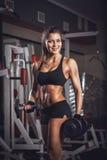 Femme sexy de forme physique avec une haltère dans le gymnase Photographie stock libre de droits