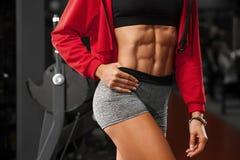 Femme sexy de forme physique montrant l'ABS et le ventre plat dans le gymnase Belle fille sportive, taille abdominale et mince fo Image libre de droits