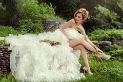 Femme sexy de jeune mariée avec de longues jambes dans la robe de mariage luxuriante Photographie stock libre de droits