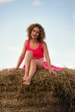 Femme sexy de mode dans la robe rouge sur la meule de foin Images stock
