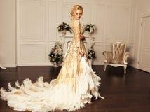Femme sexy magnifique avec les cheveux blonds dans la robe beige luxueuse images stock