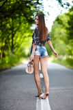 Femme sexy marchant le long de la route Photographie stock