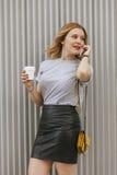 Femme sexy parlant à son téléphone tout en buvant du café Photos stock