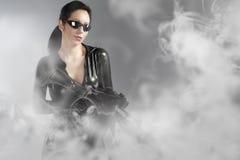 Femme retenant le canon avec le casque au-dessus de la fumée Photos libres de droits