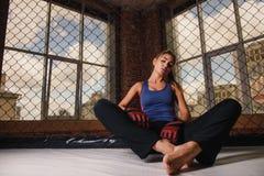 Femme sexy s'asseyant au plancher de gymnase photo libre de droits