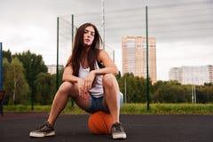 Femme sexy s'asseyant sur le basket-ball Photographie stock libre de droits