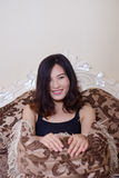 Femme sexy s'asseyant sur un divan Images libres de droits