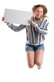 Femme sexy sautante avec un conseil blanc vide d'isolement sur le blanc Image libre de droits
