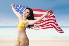 Femme tenant le drapeau américain à la plage Photos stock