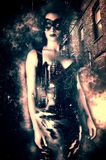 Femme sexy utilisant un masque vénitien et un costume serré de latex dans une allée foncée de ville Photos stock