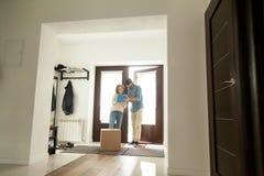 Femme signant pour le colis recevant la boîte du messager à la maison photos stock