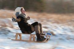Femme sledging en bas de la scène de colline, lumineuse et joyeuse d'hiver Photographie stock libre de droits