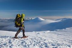 Femme snowshoeing en montagnes carpathiennes d'hiver Image stock