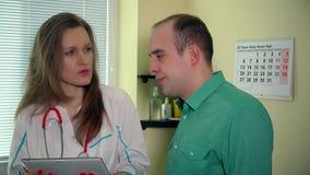Femme soigneuse de médecin donnant des résultats d'essai patients tristes d'homme sur le comprimé numérique banque de vidéos